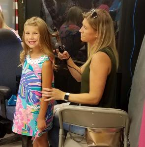 Lindsey Coffelt styles her daughter MaKinley's hair.